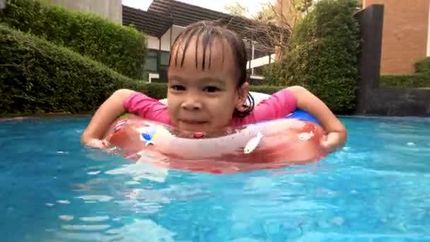 Veselý asijské malé dítě dívka hrát v bazénu s rodinou v letním dni. Rodinný životní styl v dovolené.