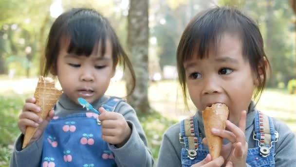 Asijské sourozenecké sestry těší jíst se zmrzlinou, sedí na trávě v parku v letní den. Koncepty šťastné rodiny a dětství.