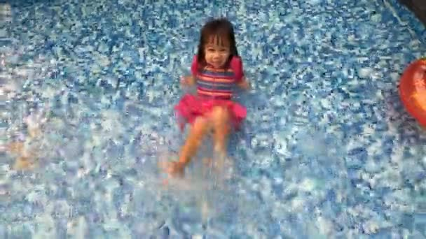Cheerful Asian little child girl playing in swimming pool with in a hot summer day. Family lifestyle in vacation.