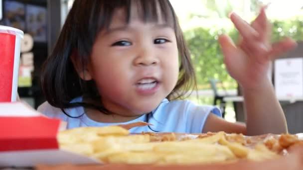 Boldog gyermek lány élvezni eszik sült csirke, sült krumpli és nektár szervizben. Junk food and Health koncepciók.
