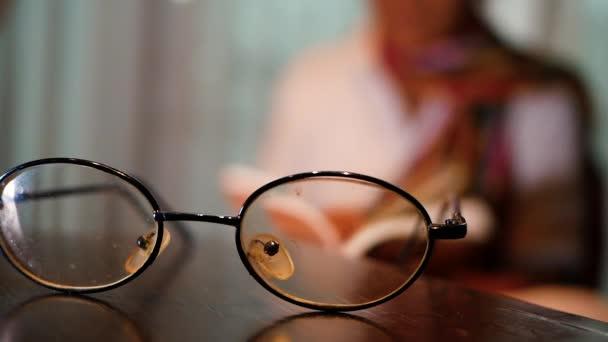 Asijský senior čte v noci na posteli knihu. Selektivní zaměření pomocí brýlí na stole.