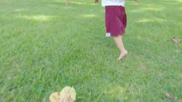 Nahaufnahme von barfüßigen Kindern, die auf der Wiese im Park im Freien laufen. Konzept des Kindheitsglücks.