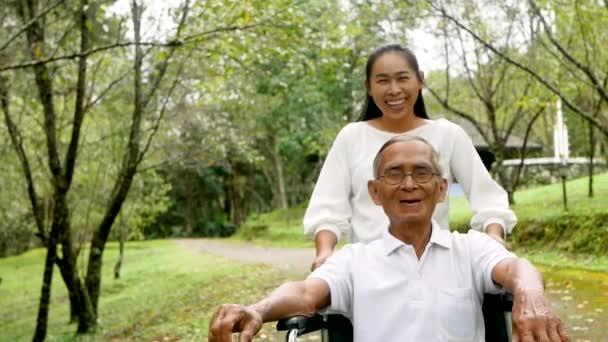 Glücklich lächelnder Opa im Rollstuhl entspannt sich und geht mit Enkelin im Park spazieren. Familienfreundlicher Lebensstil.