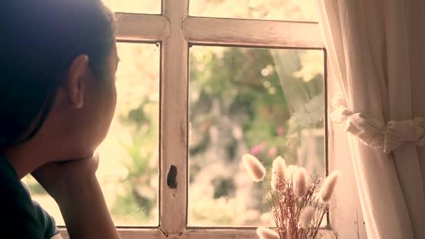Zblízka vyobrazený portrét ženy, sedící otupěle a dívající se ven skleněnými okny domů. Emocionální osamělost. Styl ročníku.