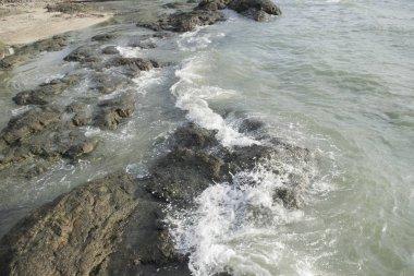 waves crashing on rocks in the beach closeup shot