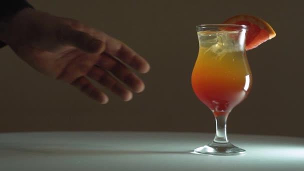 Die Hand eines Mannes holt einen Fruchtcocktail aus dem Rahmen. Orange-roter Cocktail mit Eis und Grapefruit. die Zeitlupe.