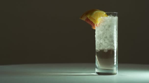 A mans hand picks up a fresh cocktail from the frame. Clear cocktail with ice, lemon, orange and grapefruit. 4k.