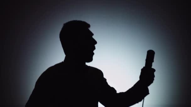Az árnyék egy férfi a világos háttér. A férfi énekel egy mikrofonba. Érzelmek, ének.
