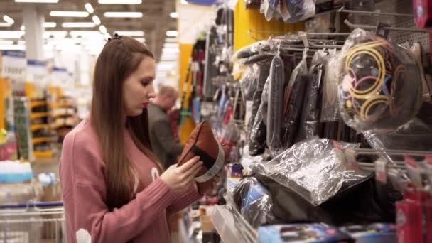 Mladá žena si vybírá polštář pro auto v supermarketu