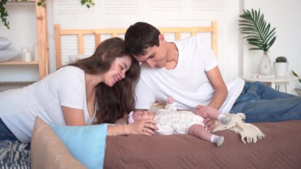Smiling family in bed where dad and mom are watching, touching and talking with their baby daughter.