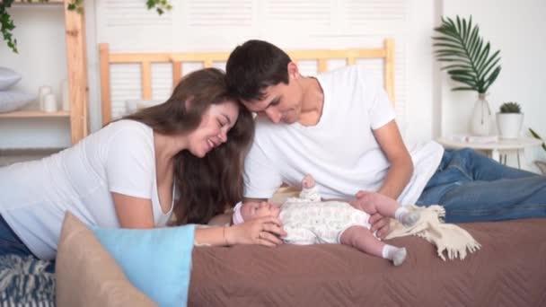 Famiglia sorridente a letto dove papà e mamma stanno guardando, toccando e parlando con la loro figlia bambino.