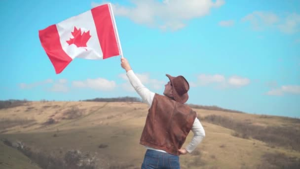 A man in a hat, vest and leather jacket and jeans holds a Canadian flag. A man stands with his back in the frame.