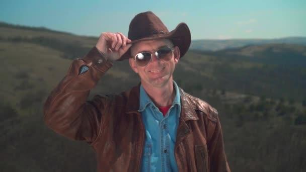 V horách, muž v kovbojské čepici, kožený kabát, brýle. Muž se dotkl klobouku rukou.