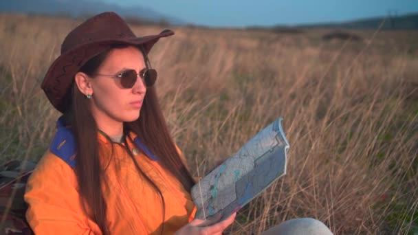 Dívka s dlouhými tmavými vlasy ve žlutém kabátku, kožený kovbojský klobouk a brýle, která se dívá na cestovní mapu.