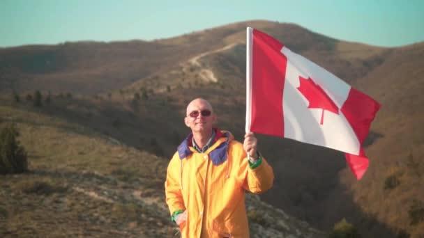 Az ember a hegyekben áll, és birtokolja a kanadai zászlót. Fényes sárga ruhákat és poharakat visel.