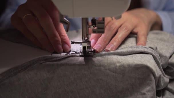 Frauenhände nähen mit einer Nähmaschine. Frauenhände nähen an einer Nähmaschine. Mode, Kreation und Schneiderei.