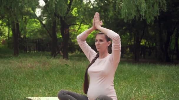 Těhotná žena trénuje jóju v parku, sedí v lotosové poloze, drží paže nad sebou a medituje.