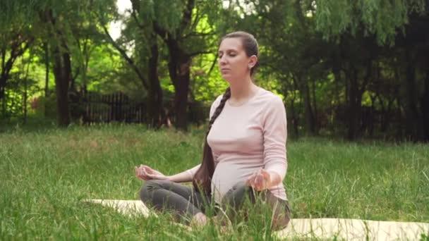 A terhes nő gyakorlatok jóga a parkban ülve egy szőnyeg, ül a lótusz helyzetben, és meditál.