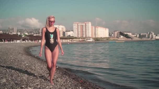 Mladá sexy holka v plavkách a šla po pláži u moře. Blondýna ve stylových slunečních brýlích a jednodílný plavky.