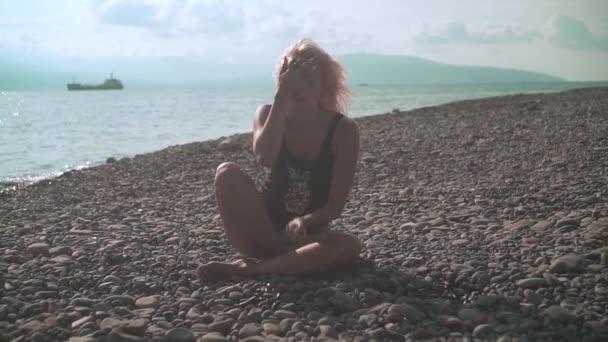 Mladá krásná sexy vyčiněná dívka v jednodílné plavkách si omyje obličej nebo se obtahy kameny.