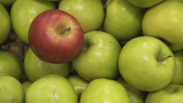 Closeup of a ripe red apple among green apples in the supermarket basket of a deli.
