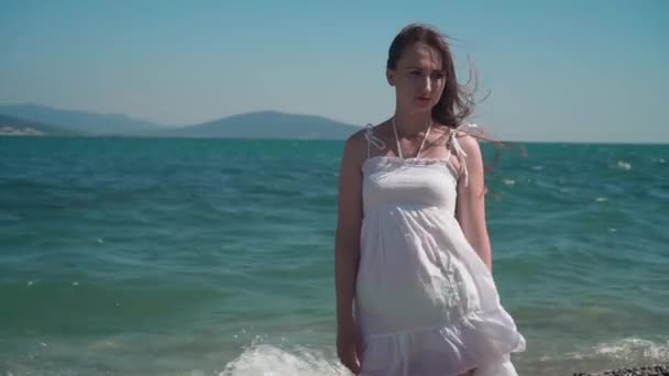 A girl in a white beach dress, walks along the seashore. A beautiful girl with bare feet walks along the seashore.