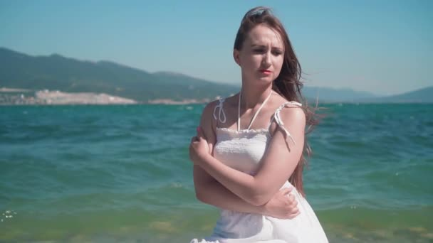 Portrait of a girl in a white dress on the seashore. Beautiful girl, lips with red lipstick, hair develops in the wind.