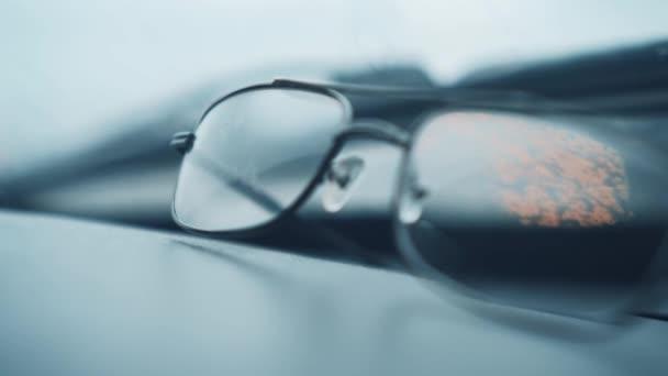 Pánské brýle pro vidění leží na šedém pozadí, v brýlích oranžová světlice