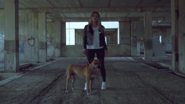 Mladá dívka se psím plemenem American Staffordshire Terrier stojí v opuštěné budově. Ta holka kouří..