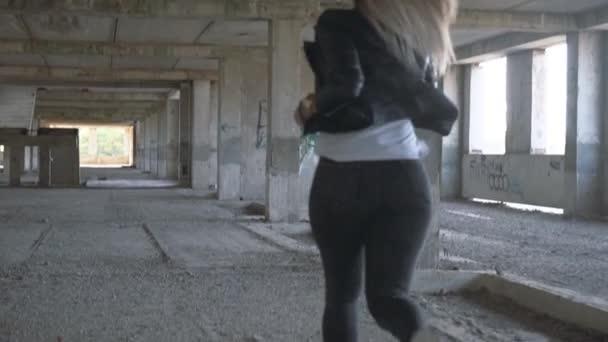 Junge Blondine mit Hunderasse American Staffordshire Terrier läuft durch ein verlassenes Gebäude.