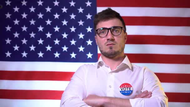 A man with glasses, with the words Voit on a shirt near his heart, against the background of the American flag. Election and voting concept