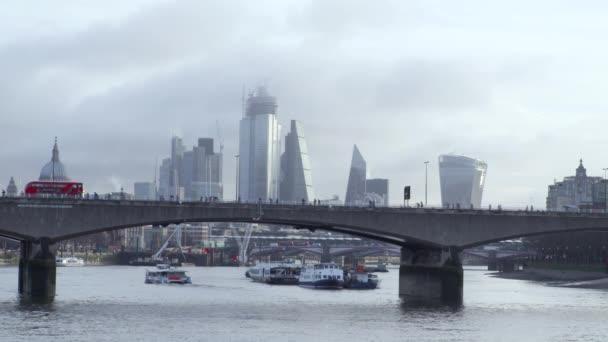 Londýnské autobusy překračují panorama města za svítání