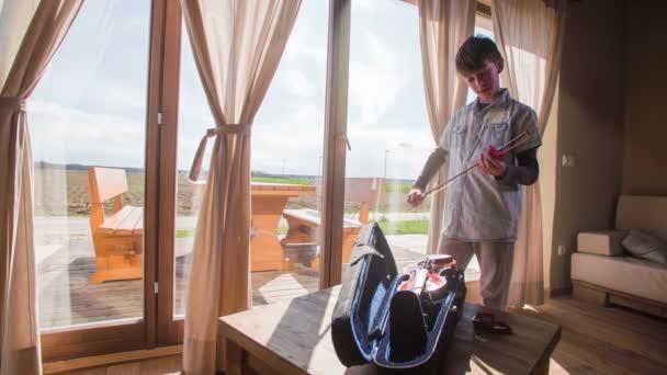 Arco da violino pulizia adolescente nel salotto 4k. Giovane ragazzo in abiti eleganti, pulizia strumento prima delluso, in piedi di fronte grandi finestre luminose con splendida natura di fuori