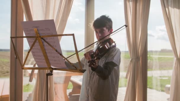 Spielen an der Violine in hellen Raum 4k. Junge, Geige zu spielen, beobachten Notizen auf Ständer, große helle Fenster im Hintergrund genießen. Fock erschossen