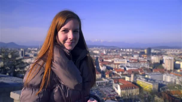 Female person with long brown hair looking in camera smiling, big city in background. Sunny day.