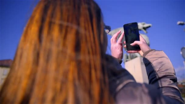 Over shoulder view of long brown hair woman holding and tapping on smartphone device on a sunny day with blue sky.