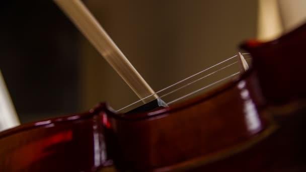 Violine und Bogen Saiten spielen Makro Nahaufnahme 4K. Person, die auf braune traditionelle Geige in Zeitlupe zu spielen. Langsame Bewegung des Bogens Reiben auf Saiten