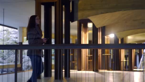 Žena s dlouhými vlasy a oblečený v teplé oblečení pomalu prohlídkou a vyfotit s smartphone s flash zářící