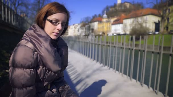 Attractive brown hair woman with glasses in warm jacket sit on bench beside city river protected with fence on a sunny day.