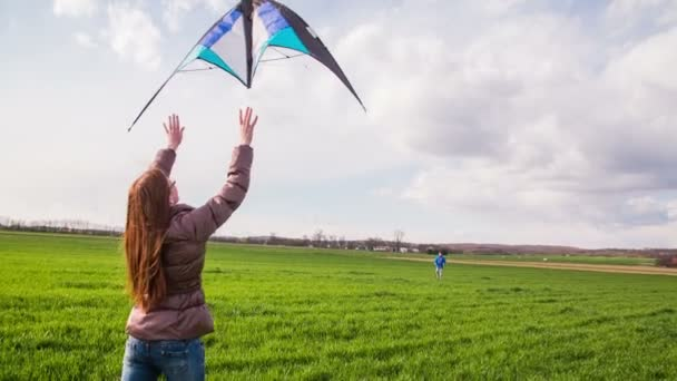 Throwing wind kite in air 4K. Girl holds wind kite, when throws it in air, boy far away runs backwards to keep it in wind. Beautiful green lawn flat land.