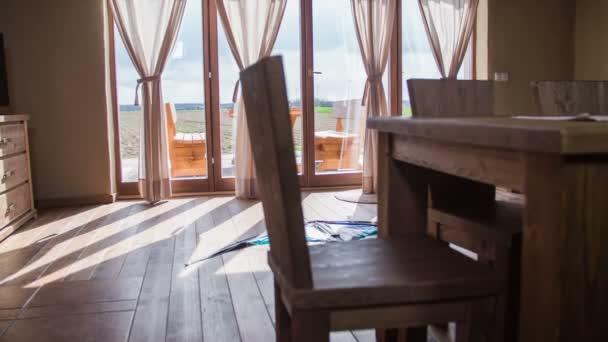 Vítr Drak ležel na podlaze krásný obývací pokoj 4k. Kosatka široký záběr na kuchyňské židle a stůl a obývací pokoj okna v pozadí s výhledem na terase slunného dne
