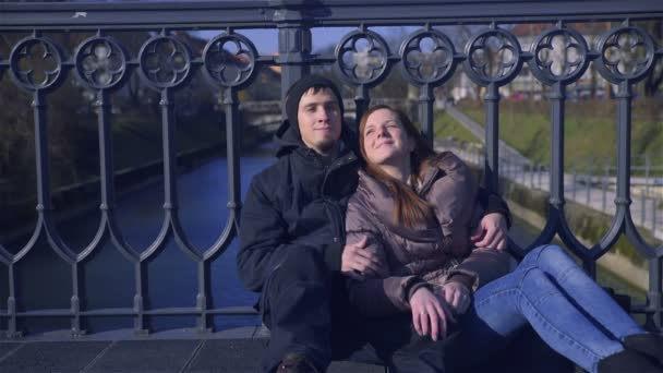 Young man and woman comforting one another, sit leaning at bridge fence. Man gives a kiss on woman cheek.