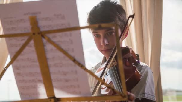 Knabe mit Geige auf Noten 4k konzentriert. Kamera-Ansicht von hinten mit Notizen mit jungen lesen und Abspielen von Musik auf Geige in Zeitlupe. Süßes Kind sehr talentiert. Üben im Wohnzimmer