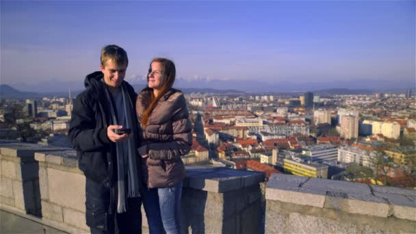 Young man holding smartphone device and take a photo with girlfriend with view on Ljubljana in background.