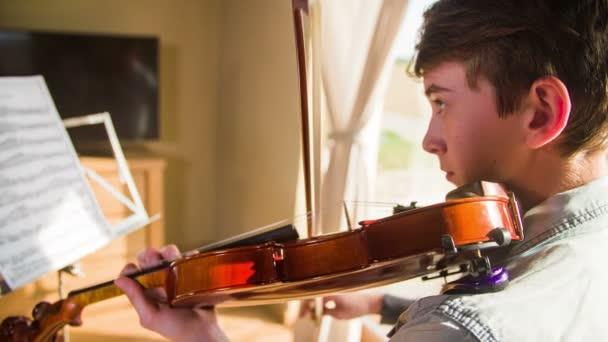 Um Geiger spielen zu Hause 4k Kamera Reisen. Junger Teenager Praxis spielen, Blick auf Notenblatt auf Stand beim schwingen mit Bogen auf Saiten professionelle traditionelle braune Geige