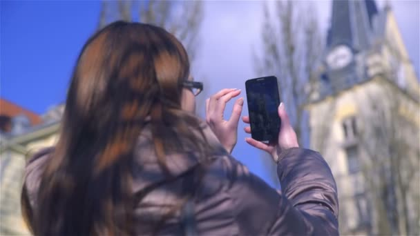 Over shoulder view of woman take photo with big black smartphone device on a sunny day. Long brown hair and dressed in warm jacket.
