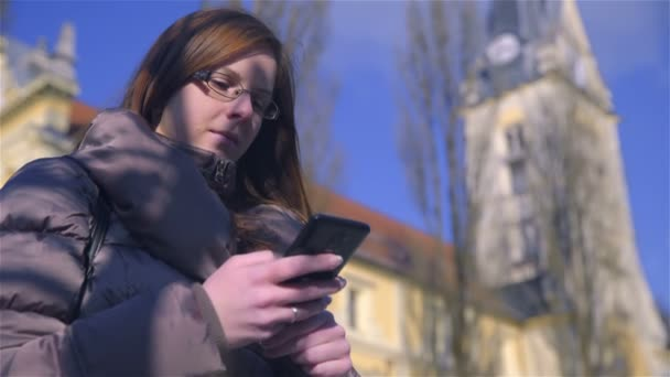 Woman with long brown hair looking at smartphone device with a church bell in background.