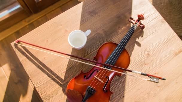 Ansicht von oben Violine auf Holztisch Folie über 4k. Verlegung auf Holztisch mit Sonne über Bogen und weißen Becher neben Violine Instrument
