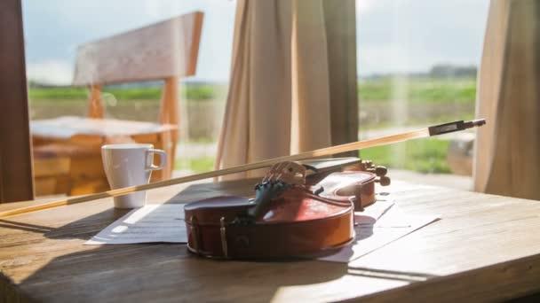 Housle, položil na stůl s hrnek s horkou kávou a zobrazit mimo 4k. Hudební nástroj na stole s bílý hrnek s kouře vyjde. Zobrazení na šířku pozadí s dřevěným sedákem mimo