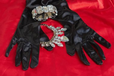 two pretty black gloves next to shiny necklace and bracelet on red background